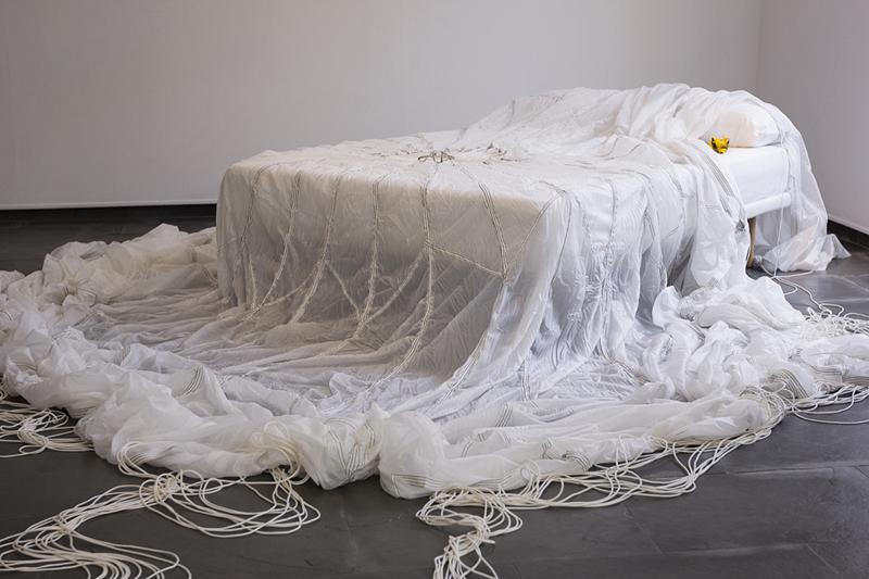 Sin título. InSin título. Instalación, paracaídas, cama y pájaro con pan de oro. 2013